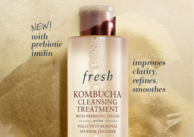 Kombucha Facial Essence bottle in front of blue sky